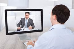 Businessman video conferencing with coworker on pc at desk Stock Images