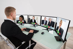 Businessman Video Conferencing On Desk Royalty Free Stock Images