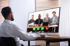 Businessman Video Conferencing With His Partner On Computer. Young Businessman Video Conferencing With His Partner On Computer At Workplace royalty free stock images
