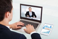 Businessman video conferencing on laptop in office Stock Photography