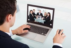 Businessman video conferencing on laptop in office Stock Images