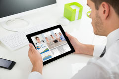 Businessman Videoconferencing With Colleagues On Digital Tablet Stock Photography