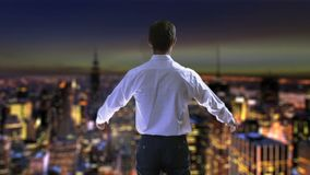 Businessman viewing night city from skyscraper, raising hands in victory success stock video footage