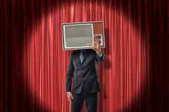 Businessman with vintage tv set instead of head making stop gesture on red stage curtains background stock photo