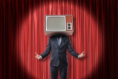 Businessman with vintage tv set instead of head on red stage curtains background stock photo