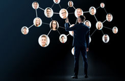Businessman with virtual corporate network. Business, people and technology concept - businessman in suit with virtual icons of corporate network over black Stock Photo