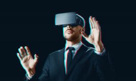 Businessman in virtual reality headset over black. Business, augmented reality and technology concept - businessman in virtual headset over black background Stock Images