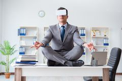 The businessman in virtual reality vr glasses meditating at desk top. Businessman in virtual reality VR glasses meditating at desk top Stock Photos