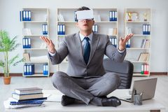 The businessman in virtual reality vr glasses meditating at desk top. Businessman in virtual reality VR glasses meditating at desk top Royalty Free Stock Photography