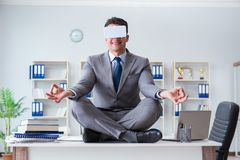 The businessman in virtual reality vr glasses meditating at desk top. Businessman in virtual reality VR glasses meditating at desk top Royalty Free Stock Images