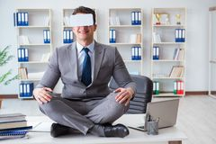 The businessman in virtual reality vr glasses meditating at desk top. Businessman in virtual reality VR glasses meditating at desk top Stock Photography