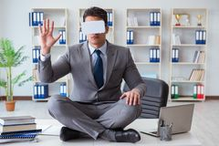 The businessman in virtual reality vr glasses meditating at desk top. Businessman in virtual reality VR glasses meditating at desk top Stock Photo