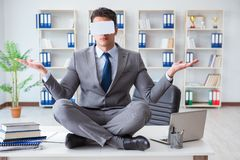 The businessman in virtual reality vr glasses meditating at desk top. Businessman in virtual reality VR glasses meditating at desk top Royalty Free Stock Image