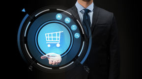 Businessman with virtual shopping cart projection Stock Photo