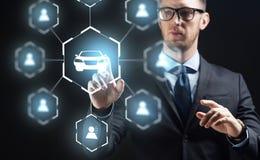 Businessman with virual hologram of car sharing stock image