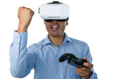 Businessman with vr glasses clenching fist while playing video game Stock Photos