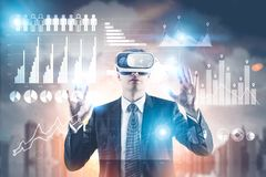 Businessman in VR glasses, infographics, city. Portrait of a young businessman wearing a suit and VR glasses and interacting with what he sees. A morning city Stock Photo