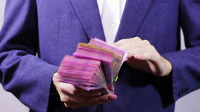 Businessman with Wads of Money in Hands. Businessman counts tens of thousands of Hryvnia (Ukrainian currency), holding them in their hands.  A man dressed in a stock video footage