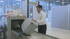 Businessman wait for luggage after scanning through x-ray scanner in the airport. Handsome businessman is in the security check room in the airport. Cute airport stock video footage