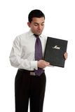 Businessman or waiter with a black folder. A professional businessman, waiter, restauranteur holding and presenting a black leatherbound folder Royalty Free Stock Photography