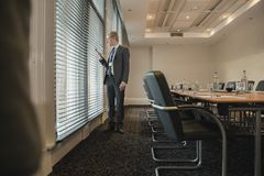 Waiting to Have a Meeting. Businessman waiting in the board room for a meeting. Looking through the blinds and window to see if people are arriving Royalty Free Stock Photo