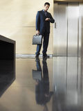 Businessman Waiting For Elevator Checking Wristwatch Stock Photo