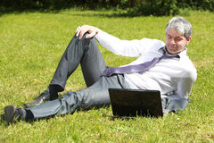 Businessman waiting the final outcome. A handsome young businessman laying on a meadow, watching and waiting for the final outcome of a business deal Royalty Free Stock Images