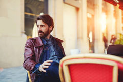 Businessman waiting for his food at the restaurant. Portrait of handsome and stylish man with beard enjoying a cup of coffee in a coffee shop, adult fashionable royalty free stock photo