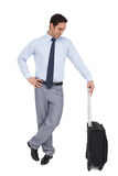 Businessman waiting while holding his luggage Royalty Free Stock Photography