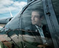 Businessman waiting inside private helicopter. Middle aged Businessman waiting inside helicopter Stock Photography