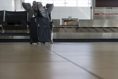 Businessman waiting for luggage in airport baggage claim area, feet up, hands behind head, low section stock photo