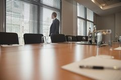 Businessman Waiting for a Meeting. Young businessman waiting to have a meeting. Stood, looking out the window in the conference room Royalty Free Stock Image
