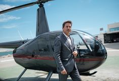 Businessman waiting near private helicopter. Middle aged businessman near helicopter Royalty Free Stock Images