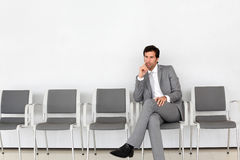 Businessman waiting sitting in hall Stock Photos