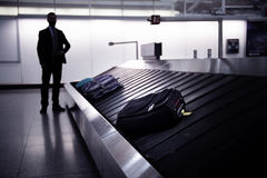 Businessman waiting for suitcase on luggage conveyor belt, airpo Stock Image