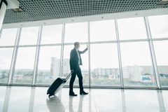 The businessman walk with a suitcase near panoramic windows in airport. The businessman walk with a suitcase near panoramic windows stock image