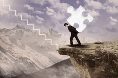 Businessman walk up carrying puzzle Stock Photo