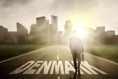 Businessman walking above Denmark word at sunrise Royalty Free Stock Photo