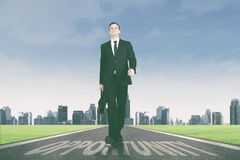 Businessman walking above opportunity word on the road. Portrait of caucasian businessman carrying a briefcase while walking above opportunity word on the road stock photos