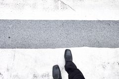 Businessman walking across the crosswalk. Black leather shoes and black slacks. Top view. stock photos