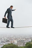 Businessman walking across a tightrope Royalty Free Stock Image