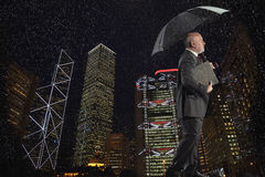 Businessman Walking Against Cityscape On A Rainy Day At Night Stock Images