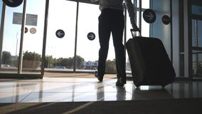 Businessman walking from the airport with his luggage. Man going through glass automatic door to the street and roll stock footage