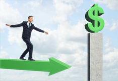 Businessman walking on arrow and get to green big dollar sign. A businessman walking on a green arrow, trying to balance himself and get to a green big dollar Royalty Free Stock Photography
