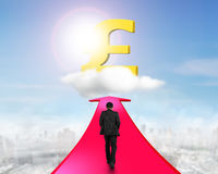 Businessman walking on arrow going toward pound symbol. Businessman walking on red arrow going upward, toward golden pound symbol on cloud in sky stock images