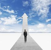 Businessman walking on arrow Stock Photos