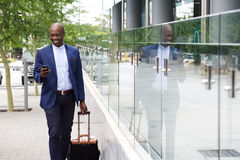 Businessman walking with bag and looking at mobile phone. Portrait of an african businessman walking with bag and looking at mobile phone Stock Image