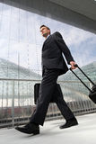 Businessman walking with bag and trolley travel Stock Photo