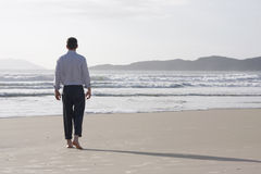 Businessman walking barefoot on a beach Stock Photography
