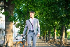 Businessman walking with bicycle Stock Photo